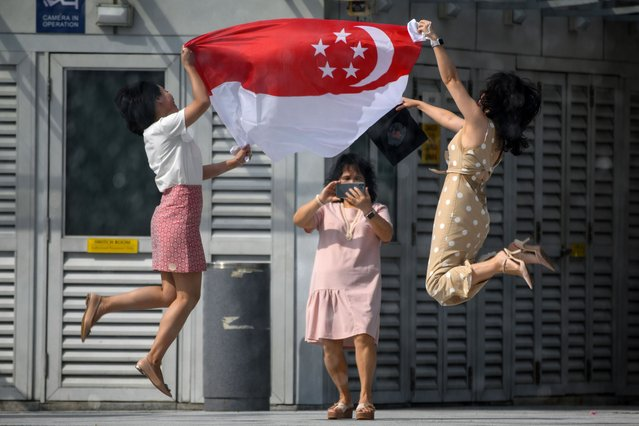 Women holding the Singapore national flag pose for a photograph at the Merlion Park to mark the 55th National Day celebrations in Singapore on August 9, 2020. National Day is celebrated in commemoration of Singapore's independence from Malaysia in 1965. (Photo by Roslan Rahman/AFP Photo)