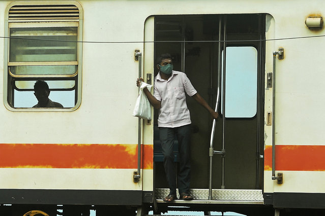 A commuter wearing a facemask as a preventive measure against the spread of the COVID-19 coronavirus, travels in a train in Colombo on July 16, 2020. (Photo by Ishara S. Kodikara/AFP Photo)