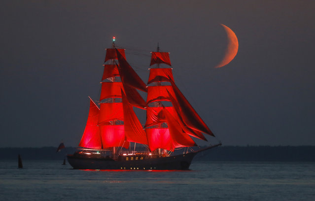 A brig with scarlet sails travels on the Finnish Gulf coast during a rehearsal for the the Scarlet Sails festivities marking school graduation which will take place on June 27 in St.Petersburg, Russia, early Friday, June 26, 2020, with the setting moon in the background. This year the festival will not be held in the city center, but on the Finnish Gulf. Due to the coronavirus pandemic, there will be no spectators but the event will be broadcast on television. (Photo by Dmitri Lovetsky/AP Photo)