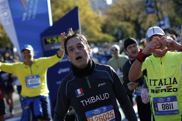 A runner reacts after crossing the finish line, November 2, 2014. (Photo by Mike Segar/Reuters)