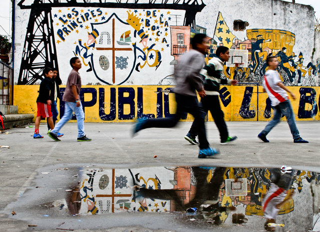"""""""After the Rain"""". Children play a game of football after a dreary morning in La Boca. Photo location: Buenos Aires, Argentina. (Photo and caption by Rebekah Lee/National Geographic Photo Contest)"""
