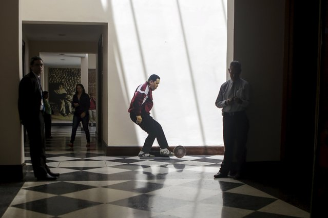 A cardboard cut-out of late Venezuela's president Hugo Chavez playing soccer is seen at the Foreign Ministry building in Caracas, Venezuela October 8, 2015. (Photo by Marco Bello/Reuters)