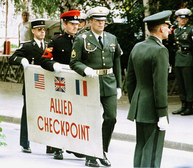 Soldiers of French, British, and American Forces carry away the sign of the Allied Checkpoint Charlie in Berlin, June 22, 1990. The sign was removed on the occasion of the removal of the allied facility at Checkpoint Charlie. (Photo by Reuters/Stringer)