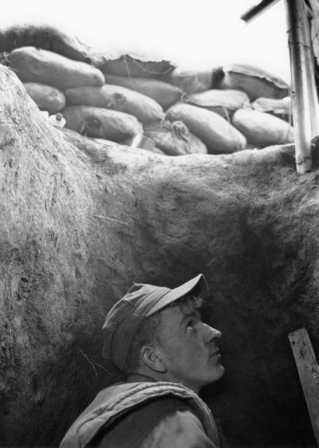 An unidentified U.S. marine looks skyward from his trench during an artillery and mortar attack on the Con Thien outpost near the DMZ in Vietnam, October 14, 1967. The sandbag revetments around the deep trenches offer relative security from shell fragments and flying shrapnel but direct hits during many days of attack have caused many casualties. The base is only two miles south of the demilitarized zone. (Photo by AP Photo)