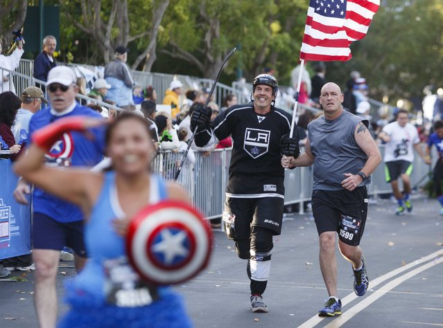 Jamie Lynch wearing an L.A. Kings hockey outfit while carrying a U.S. flag with Ethan Boyce (R) approaches the finish line of the Avengers Super Heroes Half Marathon in and around the Disney Parks in Anaheim, California November 16, 2014. (Photo by Eugene Garcia/Reuters)