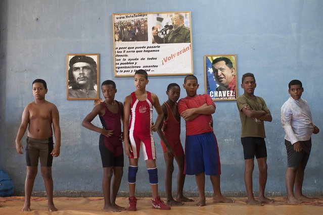 """Children make a line during a wrestling training session in front of pictures of late Cuban revolutionary hero Ernesto """"Che"""" Guevara (L),  former Cuban President Fidel Castro (C) and Venezuela's late President Hugo Chavez, on the outskirts of Havana, November 1, 2014. (Photo by Alexandre Meneghini/Reuters)"""