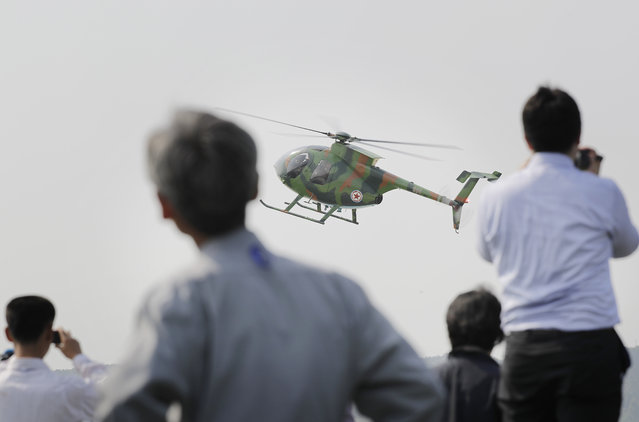 North Koreans watch a Hughes MD-500 helicopter fly past during an aerial display on Saturday, September 24, 2016, in Wonsan, North Korea. (Photo by Wong Maye-E/AP Photo)