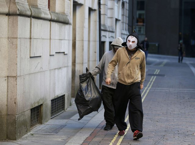 Squatters wearing face masks walk outside the former stock exchange building in Manchester northern Britain, October 19 , 2015. Homeless squatters who have occupied the building have been allowed to stay there over the winter by it's owners, including former Manchester United players Gary Neville and Ryan Giggs. The building is being renovated and transformed into a boutique hotel according to local media. (Photo by Andrew Yates/Reuters)