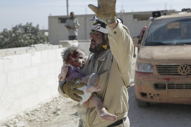 A civil defence member carries an injured baby that survived from under debris at a site hit by what activists said was an airstrike by forces loyal to Syria's President Bashar al-Assad, in the town of Marshamsha, in the southern countryside of Idlib, Syria October 20, 2015. (Photo by Khalil Ashawi/Reuters)