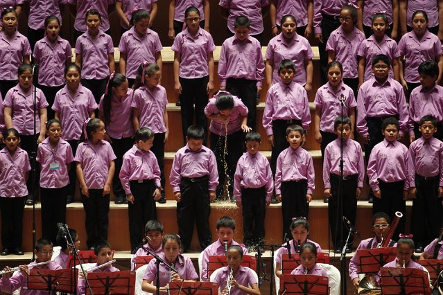 """A young member of the choir of """"Sinfonia por el Peru"""" vomits before performing with Peruvian tenor Juan Diego Florez at Lima's National Theatre, in this May 13, 2014 file photo. I was covering a concert at Lima's National Theatre, awaiting the appearance of Peruvian tenor Juan Diego Florez, who was singing with the young members of the orchestra he was sponsoring, """"Sinfonia por el Peru"""". (Photo and caption by Enrique Castro-Mendivil/Reuters)"""