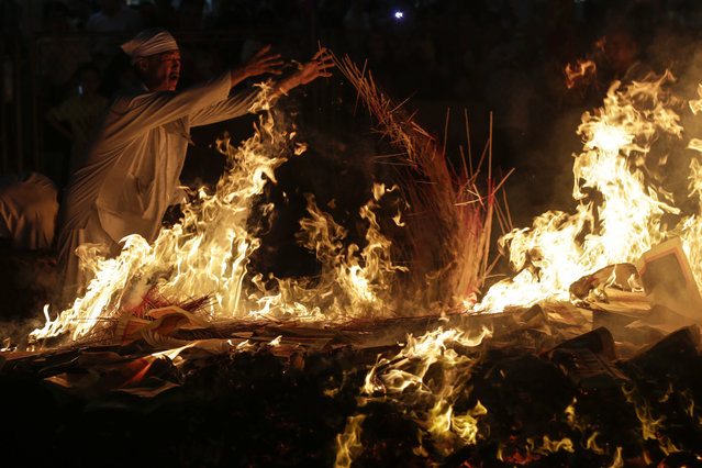 Malaysian ethnic Chinese throw jossticks on the burning charcoal on the last day of the Nine Emperor Gods festival in Kuala Lumpur, Malaysia, October 21, 2015. During the celebration, temples are packed with worshippers and hawkers selling religious items. Chinese operas are held for the Nine Emperor God who are believed to control the prosperity and health of worshippers. The festival of the Nine Emperor Gods falls on the ninth day of the ninth moon in the Chinese lunar calendar. (Photo by Fazry Ismail/EPA)