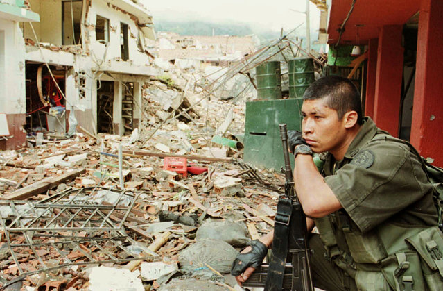 A Colombian policeman rests on his Galil rifle after a combat against rebels of the FARC in Granada city, Antioquia province, December 7, 2000. (Photo by Reuters/Stringer)