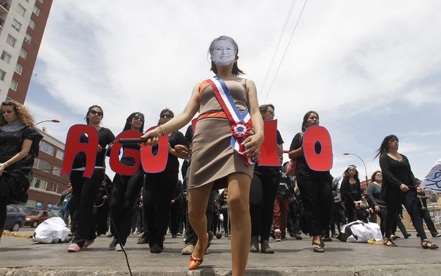 """A teacher wearing a mask of Chilean President Michelle Bachelet takes part in a rally against the government to demand an increase in their salaries in Valparaiso city, northwest of Santigo November 27, 2014. The word reads, """"Burden"""". (Photo by Rodrigo Garrido/Reuters)"""