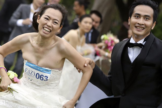 """A man and his fiancee run to victory during the """"Running of the Brides"""" race in a park in Bangkok November 29, 2014. (Photo by Damir Sagolj/Reuters)"""