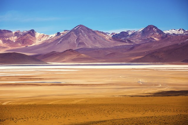 A dirt road winds through the colorful yet barren Salvador Dali desert in the Eduardo Avaroa Andean Fauna National Reserve of southwest Bolivia. (Photo by Eric Hanson/Getty Images)