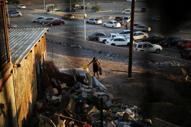 A Haitian migrant walks near garbage at the Hotel del Migrante shelter after leaving Brazil, where she relocated to after Haiti's 2010 earthquake, in Mexicali, Mexico, October 5, 2016. (Photo by Edgard Garrido/Reuters)