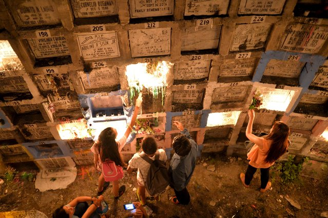 "Filipinos visit the graves of their deceased loved ones, buried in ""apartment style"" tombs, inside a public cemetery in Marikina city, east of Manila November 1, 2015. (Photo by Ezra Acayan/Reuters)"