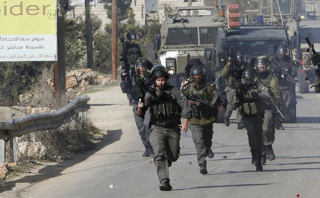 Israeli border policemen run during clashes with Palestinians in the West Bank village of Beit Ommar, north of Hebron November 3, 2015. (Photo by Mussa Qawasma/Reuters)
