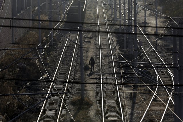 Local villagers walk along railways, which are used to transfer coal, at Zhengyang coal mine from the state-owned Longmay Group on the outskirts of Jixi, in Heilongjiang province, China, October 22, 2015. (Photo by Jason Lee/Reuters)
