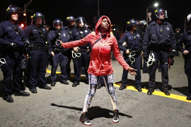 A woman pleads to be released by the police after she was surrounded during an evening demonstration against police violence in Oakland, California December 13, 2014. Decisions by grand juries to return no indictments against the officers involved in the deaths of Michael Brown in Missouri and Eric Garner in New York have put police treatment of minorities back on the national agenda. Police in Oakland, California, ordered hundreds of demonstrators to disperse on Saturday night after a grocery store was looted. (Photo by Stephen Lam/Reuters)