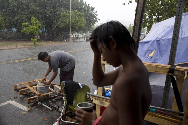 """In this Wednesday, August 26, 2015 photo, a boy who goes by """"M.J.,"""" is soaked in rain as a woman pulls nails from a pallet to use them to build a makeshift tent at a homeless encampment in the Kakaako district of Honolulu. The camp, one of the nation's largest homeless encampment and once home to hundreds of people, recently cleared by Hawaii officials. (Photo by Jae C. Hong/AP Photo)"""
