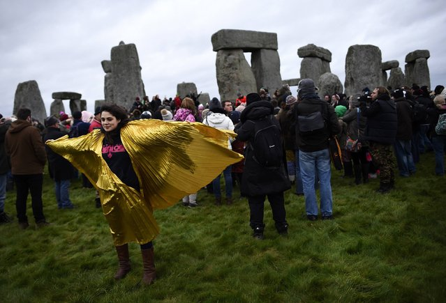 A reveller wearing a golden cape celebrates as the sun rises during the winter solstice at Stonehenge on Salisbury plain in southern England December 22, 2014. The winter solstice is the shortest day of the year, and the longest night of the year. (Photo by Dylan Martinez/Reuters)