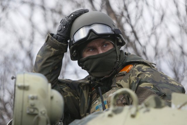 Ukrainian serviceman sits atop an armored personnel carrier (APC) at a checkpoint near the eastern Ukrainian town of Debaltseve in Donetsk region, December 24, 2014. (Photo by Valentyn Ogirenko/Reuters)