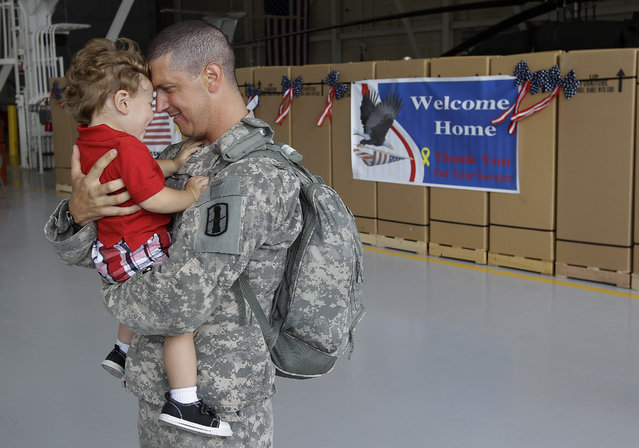 Cpt. Brian Fielder, commander of the Rhode Island National Guard's 1207th support company hugs his son Hoah, 19 months, upon his return from a one year deployment in Kuwait, where his unit oversaw security for convoys moving in and out of Iraq, in North Kingstown, RI., Friday afternoon, August 19, 2011. (Photo by Stephan Savoia/AP Photo)