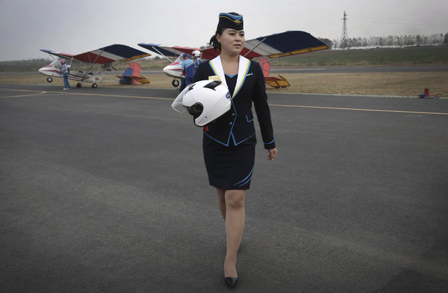 """A staff member of the Mirim Air Club carries a helmet as she walks across the tarmac at the Mirim Air Club on Sunday, October 16, 2016, in Pyongyang, North Korea. Until a few months ago, if you wanted a bird's eye view of North Korea's capital there was basically only one option: a 150-meter tall tower across the river from Kim Il Sung Square. With the support of North Korean leader Kim Jong Un, who has vowed to give North Koreans more modern and """"cultured"""" ways to spend their leisure time, a Pyongyang flying club has started offering short flights over some of the capital's major sights. (Photo by Wong Maye-E/AP Photo)"""