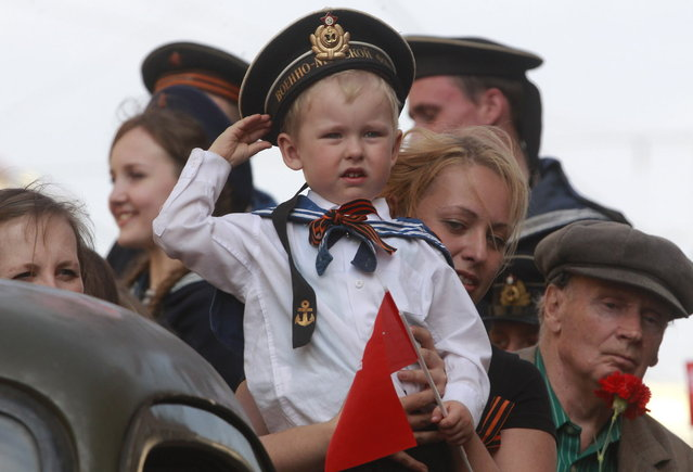 A child wearing Soviet Navy style uniform salutes during celebration of the Victory Day in St.Petersburg, Russia, Thursday, May 9, 2013. Russia is celebrating the anniversary of victory over Germany in WWII. (Photo by Dmitry Lovetsky/AP Photo)