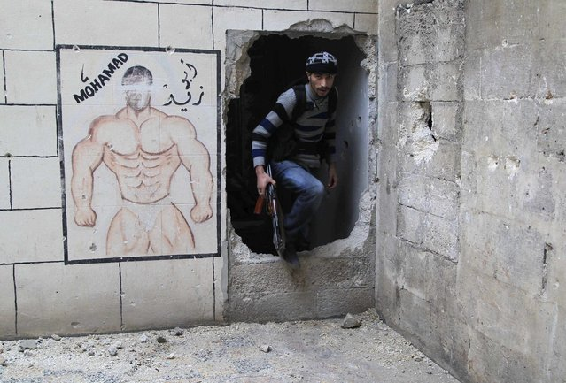 A rebel fighter carries his weapon as he moves through a hole in a wall in the old city of Aleppo near the frontline against forces loyal to Syria's President Bashar al-Assad December 28, 2014. (Photo by Jalal Al-Mamo/Reuters)