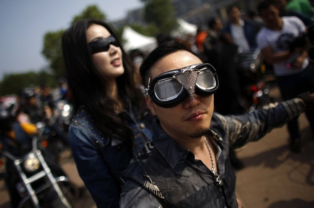A couple rides a Harley Davidson motorcycle during the annual Harley Davidson National Rally in Qian Dao Lake, in Zhejiang Province May 11, 2013. Around 1,000 Harley Davidson enthusiasts from all over China met to celebrate the 5th Harley Davidson National Rally in China, as part of the company's 110-year anniversary. Major Chinese cities ban motorcycles from circulating on highways and major avenues. Meanwhile, Harley Davidson motorbikes are considered by Chinese tax authorities to be luxury items, so they are taxed at extremely high rates – sometimes the taxes alone is equivalent to the bike's U.S. price tag. Traffic and transportation authorities have also weighed in, putting Harleys in the same category as electric bikes, horses and bicycles, meaning that they cannot be on highways and major avenues. (Photo by Carlos Barria/Reuters)