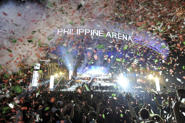 Confetti falls on revellers at midnight during New Year celebrations outside the Philippine Arena in Bocaue town, Bulacan province, north of Manila January 1, 2015. (Photo by Ezra Acayan/Reuters)