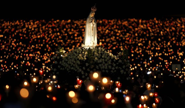 A statue of Our Lady of Fatima is carried during a candlelight vigil at the Fatima Sanctuary in Fatima, Portugal, on May 12, 2013. Every year on May 12 and 13, thousands of Catholic faithful pilgrimage to Fatima's Sanctuary where it is believed the Virgin Mary was witnessed by three shepherd children, Lucia, Jacinta and Francisco, on May 13, 1917. (Photo by Francisco Seco/Associated Press)