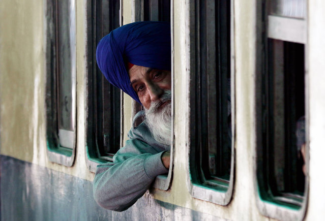A Sikh pilgrim looks on from a special train as it arrives at Wagah railway station in Wagah, Pakistan, November 20, 2015. Every year thousands of Sikhs from different parts of the world visit Pakistan to celebrate the birth anniversary of Baba Guru Nanak, founder of the Sikh Religion (born in 1469), in Nankana Sahib, Pakistan. (Photo by Rahat Dar/EPA)