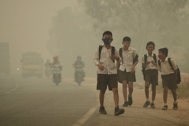 Students walk along a street as they are released from school to return home earlier due to the haze in Jambi, Indonesia's Jambi province, September 29, 2015. (Photo by Wahdi Setiawan/Reuters/Antara Foto)