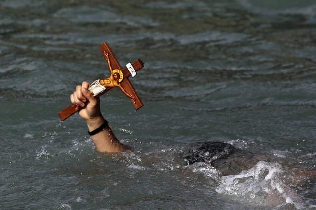 A man holds a cross after a competition to retrieve it from the water during Epiphany day celebrations in the port village of Zygi, near Limassol January 6, 2015. Orthodox priests throughout the country bless the waters by throwing a cross into it as worshippers try to retrieve it. (Photo by Yiannis Kourtoglou/Reuters)