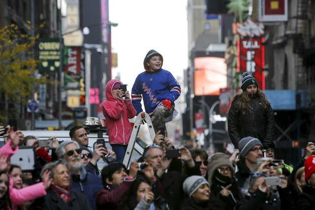 A child watches the 89th Macy's Thanksgiving Day Parade from a ladder in the Manhattan borough of New York, November 26, 2015. (Photo by Andrew Kelly/Reuters)