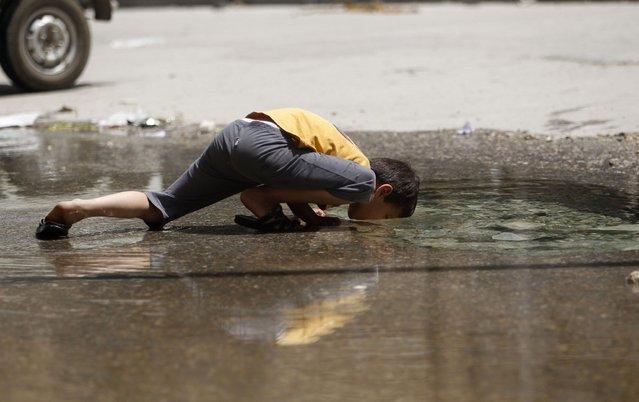 A boy drinks water from a burst water pipe in Aleppo's Karm al-Jabal district, June 2, 2013. (Photo by Muzaffar Salman/Reuters)