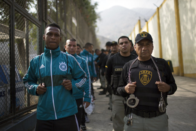 Escorted by prison guards, inmates of a football team wait in a line before the start of a soccer match in the San Juan de Lurigancho prison, in Lima, Peru, Thursday, May 24, 2018. (Photoby Rodrigo Abd/AP Photo)
