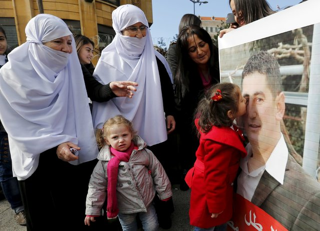 The daughter of Druze policeman Wael Hamzeh Homs, who was captured in Arsal by the al Qaeda-linked Nusra Front, kisses his picture as relatives react in celebration for his release, outside a tent that was erected last year during an open-ended sit-in near the government palace in downtown Beirut, December 1, 2015. Al-Qaeda's Syrian wing, the Nusra Front, released Lebanese security personnel held captive since August, 2014 in a swap deal that will also release an ex-wife of Islamic State leader Abu Bakr al-Baghdadi, live TV footage showed on Tuesday. (Photo by Jamal Saidi/Reuters)