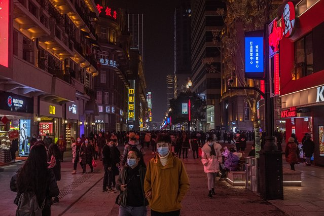 People wearing protective face masks walk in a commercial street, in Wuhan, China, 22 January 2021. The 23 January 2021 marks the one-year anniversary of the start of a strict 76-day lockdown of the Chinese city of Wuhan, where the coronavirus was first discovered before spreading across the world into a deadly global Covid-19 pandemic. (Photo by Roman Pilipey/EPA/EFE)