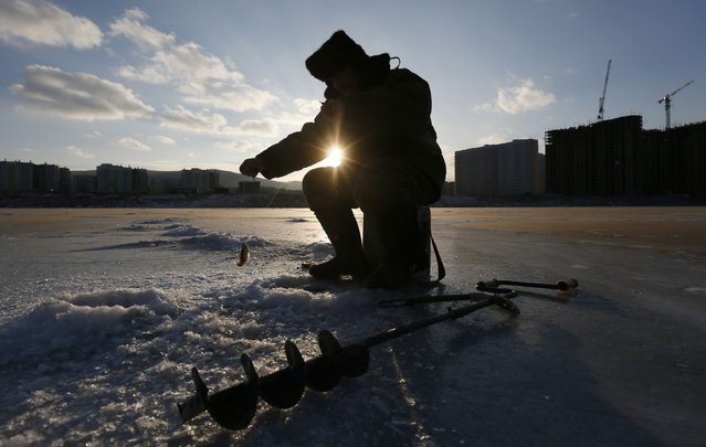 A man pulls out a Ruffe from an ice hole as he fishes on the frozen Abakan Bay of the Yenisei River in Russia's Siberian city of Krasnoyarsk January 11, 2015. (Photo by Ilya Naymushin/Reuters)