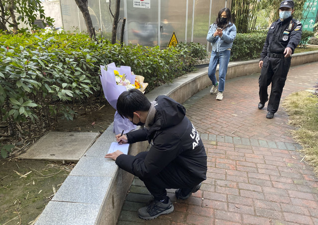 """A security guard stands neaby as a man visiting the Wuhan Central Hospital leaves flowers in memory of Li Wenliang, the whistleblower doctor who sounded the alarm and was reprimanded by local police for it in the early days of Wuhan's pandemic, prior to the anniversary of his death, in central China's Hubei province, Saturday, February 6, 2021.  Dr. Li Wenliang died in the early hours of Feb. 7 from the virus first detected in this Chinese city. A small stream of people marked the anniversary at the hospital. The 34-year-old became a beloved figure and a potent symbol in China after it was revealed that he was one the whistleblowers who authorities had punished early for """"spreading rumors"""" about a SARS-like virus. (Photo by Ng Han Guan/AP Photo)"""
