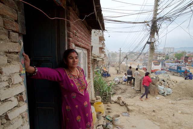"""Rambika Thapa Magar stands outside her one room home on the edge of Kathmandu's ring road. The expanded road is due to cut through the middle of the house. """"We have been told to evacuate. The demolition could started at any time, maybe while we are sleeping. We have nowhere else to go"""", said Rambika. (Photo by Pete Pattisson/The Guardian)"""
