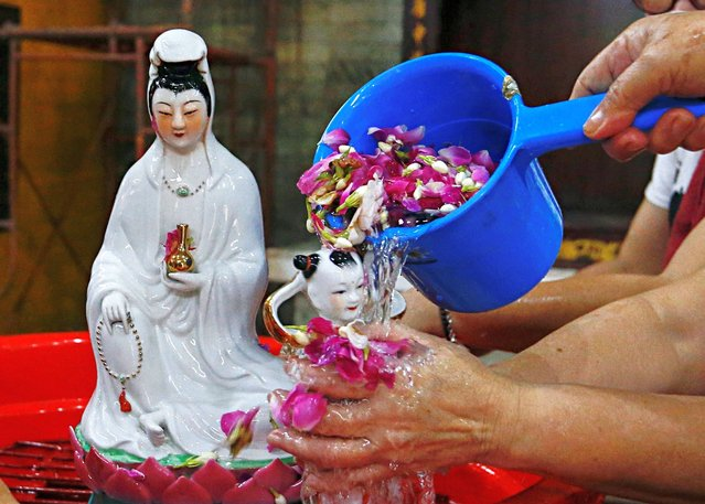 Women wash a religious figurine ahead of the Chinese Lunar New Year celebration following the coronavirus disease (COVID-19) outbreak, at a temple in Jakarta, Indonesia, February 4, 2021. (Photo by Ajeng Dinar Ulfiana/Reuters)