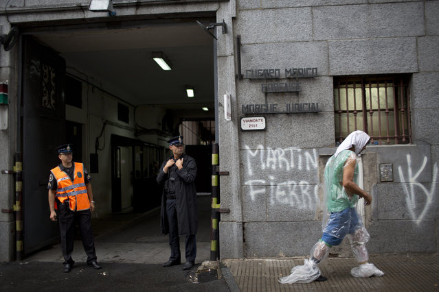 Police officers stand outside the morgue where forensic experts were conducting the autopsy on the body of  prosecutor Alberto Nisman in Buenos Aires  Monday, January 19, 2015. Special prosecutor Alberto Nisman who accused the government of secret deals with Iran over an investigation into a 1994 terrorist attack was found shot dead at his apartment early Monday. (Photo by Rodrigo Abd/AP Photo)