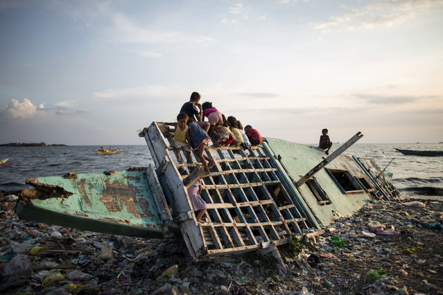Children play on a wooden boat in Manila Bay on May 10, 2018. The Philippine economy grew by 6.8 percent from a year earlier in the three months to March, in line with most expectations though there are rising concerns over inflation, the government said on May 10. (Photo by Noel Celis/AFP Photo)