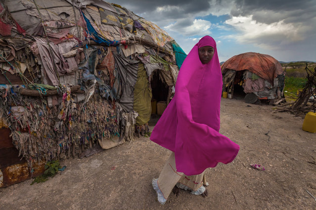 """""""My House"""". Photo of Amna a somalian girl standing in front of her small house made from a tiny woods and clothes, living with her parents and her nine brothers and sisters. Photo taken in monday 24th of septemper 2012 during a Surgical camp from Kuwait. Location: Borama, Somalia. (Photo and caption by Mohammed Alsultan/National Geographic Traveler Photo Contest)"""