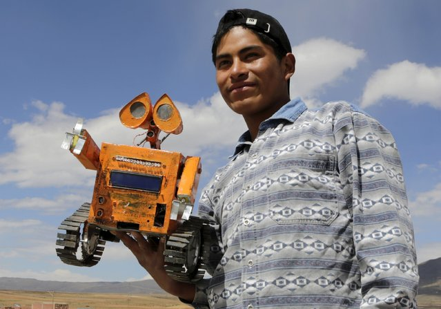 Bolivian student Esteban Quispe, 17, holds a replica of the Wall-E character in Patacamaya, south of La Paz, December 10, 2015. Quispe built the Wall-E robot using materials he obtained from a rubbish dump in the town located in the Andean highland region. He hopes to mechanize agriculture in Patacamaya by making use of robots that operate on solar energy, Quispe told Reuters. (Photo by David Mercado/Reuters)